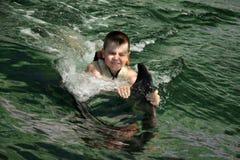 Jungenschwimmen mit Delphinnahaufnahme stockfoto
