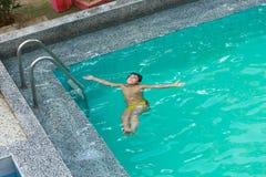 Jungenschwimmen am Pool stockbild