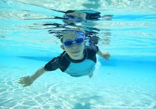 Jungenschwimmen, Unterwasserschuß stockfotografie