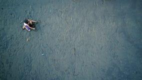 Jungenspiel auf Sand mit dunklem Schatten Lizenzfreie Stockfotografie