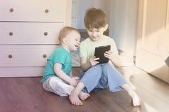 Jungenspiel in der zusammen lachenden Tablette Stockfotos