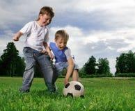 Jungenspiel im Fußball Stockbild