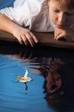 Jungenspiel mit Blattschiff im Wasser lizenzfreie stockfotos
