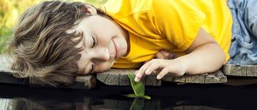 Jungenspiel mit Herbstblattschiff im Wasser, Kinder im Park spielen w stockfotos