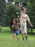 Jungenspiel mit runder Samenkapsel Stockfotos