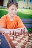 Jungenspiel Schach mit Konzentration Lizenzfreie Stockfotos