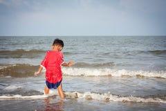 Jungenspiel am Strand Stockfotos