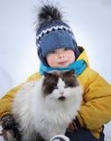 Jungenspiele mit einer Katze draußen Lizenzfreie Stockbilder