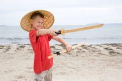 Jungenspiele mit einer Samuraiklinge Lizenzfreies Stockfoto
