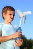 Jungenspiele mit windbetriebenem Generator Stockfotos