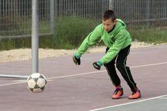 Jungenspielfußball im Schulhof Stockfotos