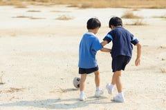 Jungenspielfußball aus den Grund des trockenen Bodens Stockbild