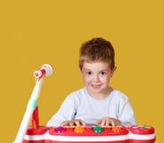 Jungenspielmusik auf Tastatur Stockfotografie
