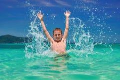 Jungenspritzwasser im Meer Spielerisches Kind 10 Jahre altes umgeben durch bunte Natur Heller blauer Himmel und schimmerndes Meer Stockfotografie
