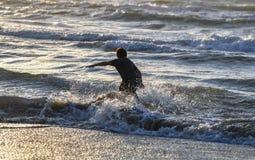 Jungenspritzwasser und Spaß auf tropischem Strand während der szenischen Sonnenuntergangansicht der Ferien des tropischen Strande stockfotografie