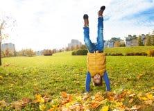 Jungenstand auf Händen auf dem Rasen Stockbilder