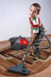 Jungenstaub mit Staubsauger Stockfotografie