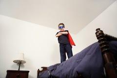 Jungensuperheld auf Bett Lizenzfreie Stockbilder