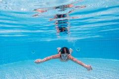 Jungentauchen im Swimmingpool stockfoto