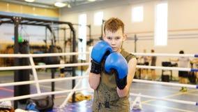 Jungenverpacken mit blauen Handschuhmachern auf dem Ring stockfotografie