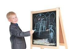 Jungenzeichnung auf einer Tafel Lizenzfreie Stockfotografie