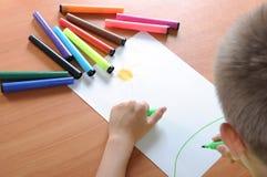Jungenzeichnung auf Papier mit Zeichenstiften Stockfotos