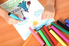 Jungenzeichnung auf Papier mit Zeichenstiften Stockbilder