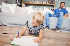 Jungenzeichnung im Buch während Vater, der auf Sofa sitzt Stockfoto