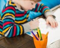 Jungenzeichnung mit Bleistiften Stockfoto