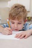 Jungenzeichnung mit einem Bleistift Lizenzfreies Stockfoto