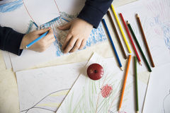 Jungenzeichnung mit Zeichenstiften am Tisch Lizenzfreie Stockbilder