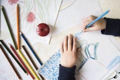 Jungenzeichnung mit Zeichenstiften am Tisch Stockfotos