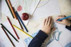 Jungenzeichnung mit Zeichenstiften am Tisch Stockfotografie