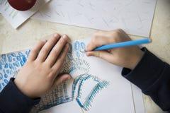 Jungenzeichnung mit Zeichenstiften am Tisch Lizenzfreie Stockfotografie