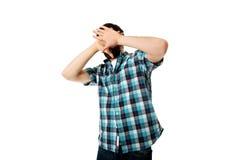 Junger ängstlichmann, der sein Gesicht bedeckt Stockbilder