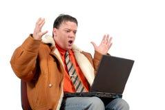 Junger überraschter schauender Geschäftsmann, der an Laptop arbeitet Lizenzfreies Stockbild