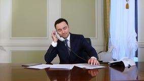 Junger überzeugter erfolgreicher Geschäftsmann, der im modernen Büro telefonisch analysiert Gespräch des Geschäfts arbeitet stock video footage
