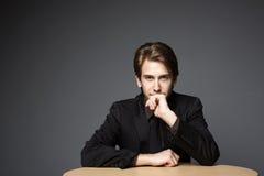 Junger überzeugter Geschäftsmann, der auf einem Schreibtisch sitzt Lizenzfreie Stockbilder