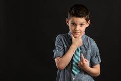 Junger überzeugter Junge mit der Hand auf Chin Stockfotos