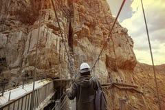 Junger abenteuerlicher Mann mit dem Sturzhelm, der eine Holzbrücke kreuzt Lizenzfreies Stockfoto