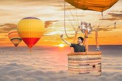 Junger Abenteuermannreisender, der selfie im Heißluftball des Korbes tut Stockbild