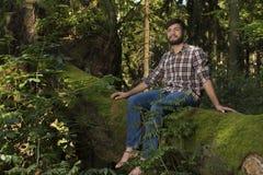 Junger Abenteurer, der auf einem Stamm genießt Natur sitzt Stockbilder