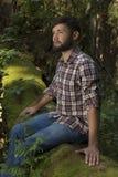 Junger Abenteurer, der auf einem Stamm genießt Natur sitzt Stockfoto