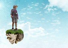 Junger Abenteurerjunge auf sich hin- und herbewegender Felsenplattform im Himmel mit Wortverbindungsstücken schließen an Stockbild