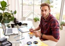 Junger aduld Geschäftsmann, der Kamera beim Arbeiten betrachtet Lizenzfreies Stockbild