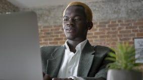 Junger afrikanischer blonder Geschäftsmann, der auf Laptop schreibt und im modernen Büro, überzeugt, lachend sitzt stock video