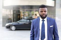 Junger afrikanischer Geschäftsmann, der sein schwarzes Auto auf den Bürovoraussetzungen lässt lizenzfreie stockfotos