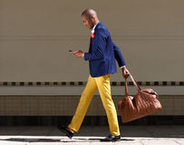 Junger afrikanischer Geschäftsmann gehende Tasche und Handy Wirth lizenzfreies stockfoto