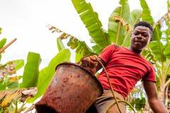 Junger afrikanischer Junge mit Eimer voll Boden während des Handbuchgrabens des Wassers gut in afrikanisches Land mit Bemühungsau lizenzfreie stockfotos