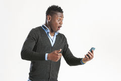 Junger afrikanischer Kerl, der Handy betrachtet Stockbild